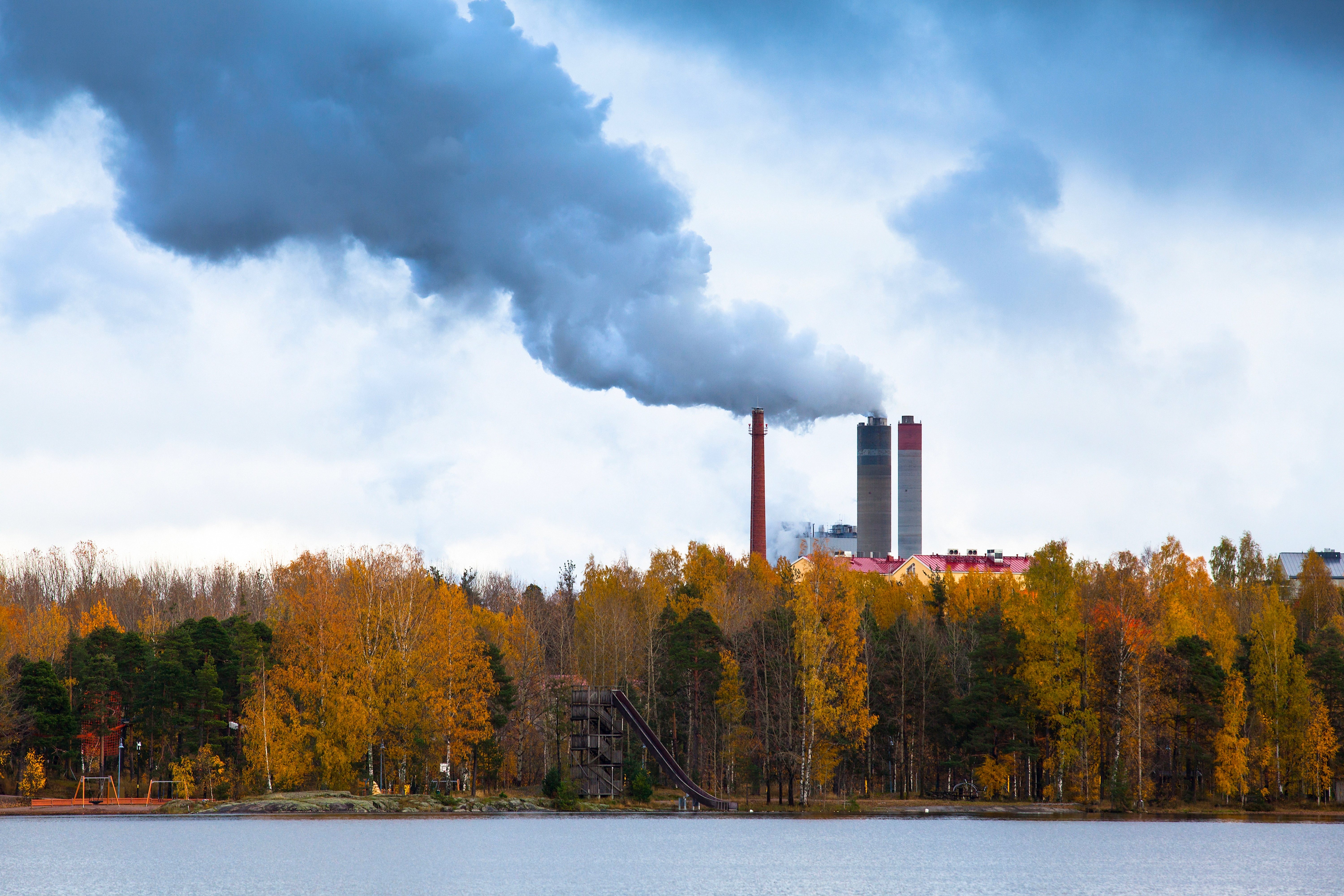 Air pollution by smoke coming out of three factory chimneys