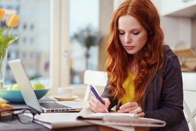 woman taking notes on laptop computer.jpg