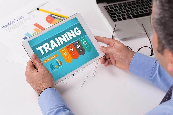 Man working on tablet, training is written on screen