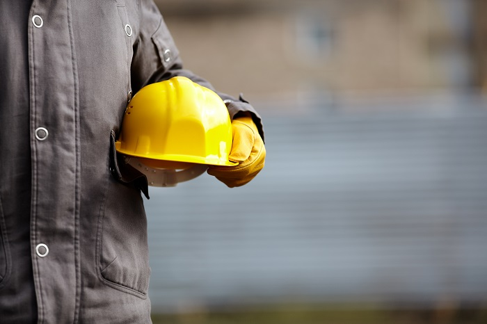 worker holding yellow helmet
